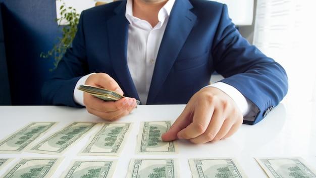 그의 사무실 책상에 돈을 계산하는 부유 한 사업가