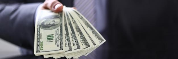 손에 지폐의 무리를 보여주는 부유 한 사업가
