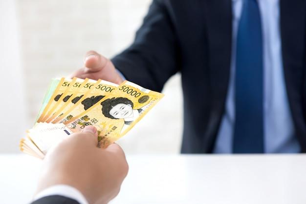 Rich businessman giving cash south korean won banknote money to his partner