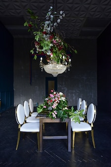 Rich christal chandelier hangs over the dinner table with red roses and greenery