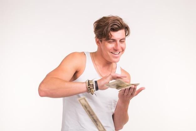 Богатая, веселая и финансовая концепция - красивый молодой человек бросает деньги на белом фоне.