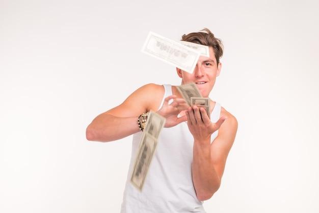 Богатая, веселая и финансовая концепция - красивый молодой человек бросает деньги на белую поверхность.