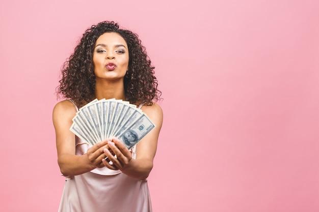 Богатая девушка! денежный победитель! удивленная красивая афро-американская женщина в платье, держащая деньги и смотрящая в камеру, изолированную на розовом фоне.
