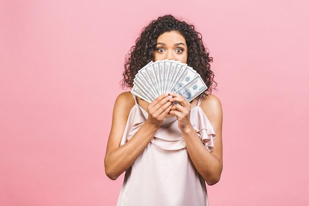 金持ちの女の子!お金の勝者!お金を保持し、ピンクの背景に対して隔離されたカメラを見てドレスを着た美しいアフリカ系アメリカ人の女性を驚かせた。