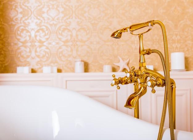 Богатый золотой смеситель и белая ванна в ванной. санитарное оборудование класса люкс