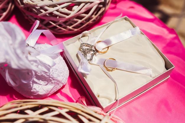 풍부한 황금 결혼 반지는 흰색 리본에 거짓말