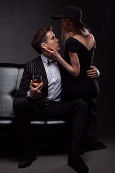 金持ちのハンサムな男は、暗い場所で夕方に金髪の愛人とウイスキーを飲みます