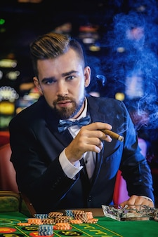 Rich handsome man smoking cigar in the casino