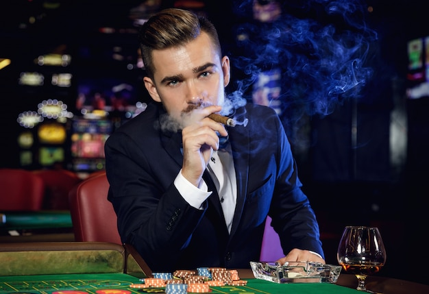 Rich handsome man smoking cigar in the casino