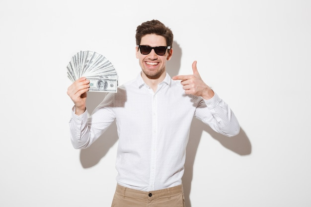 Rich and happy man in shirt and sunglasses rejoicing and pointing finger on lots of money dollar cash, isolated over white wall with shadow