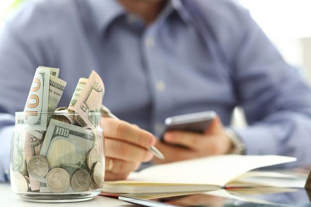 豊富な瓶いっぱいまたは米国の紙幣と彼の携帯電話で経費を数えるバックグラウンドで実業家の腕を持つコイン