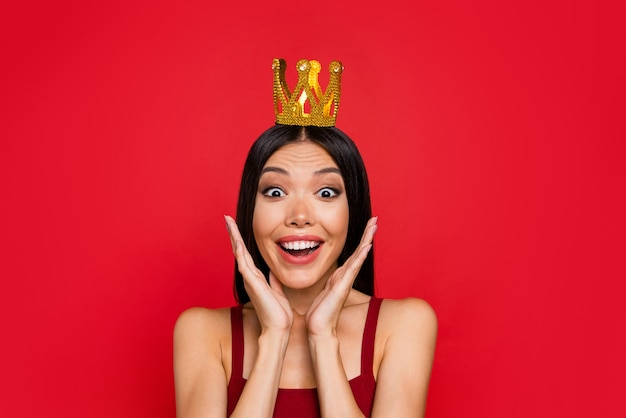 Rich lady tiara on head open mouth staring eyes on red wall