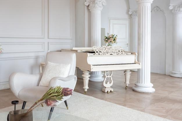 바로크 기둥과 벽에 치장 벽토로 장식된 현대적이고 세련된 가구와 그랜드 피아노가 있는 아늑한 객실의 풍부하고 고급스러운 인테리어