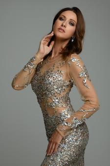 豊かな豪華な孤立した茶色の髪緑目ファッションは、豪華なスパンコールのついたドレスと官能的な性的ポーズで立っているイヤリングで美しいスリムな女性を構成します。