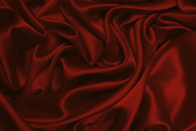 Rich and luxury red silk fabric texture background. top view.
