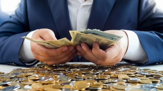 Rich man hands holding stack of money on heap of coins. concept of financial investment, economy growth and bank savings.
