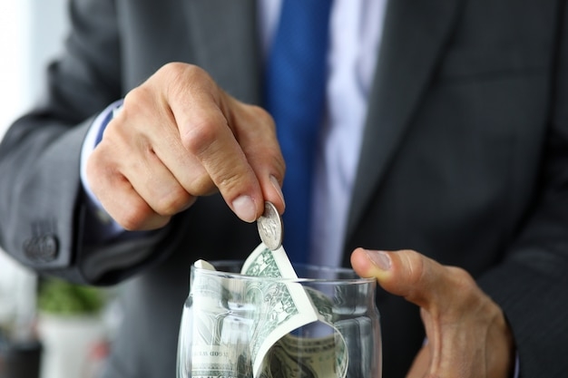 Rich man in suit and tie put extra coin into jar full of us dollars
