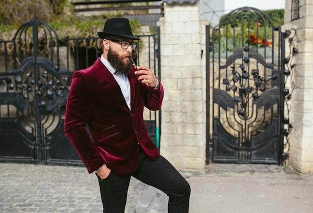 Un uomo ricco con la barba fuma la culla