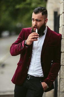 Un uomo ricco con la barba fuma sigaretta elettronica electronic