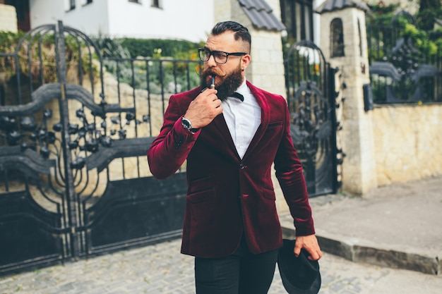 A rich man with a beard smokes electronic cigarette
