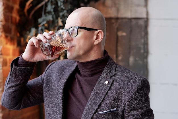 Богатый лысый мужчина средних лет в очках стоит в ресторане-лофте и пьет алкоголь из стекла