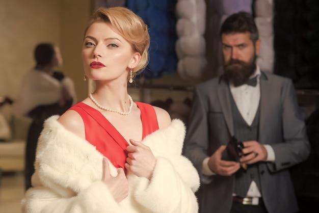 金持ち。贅沢な生活。男性、ショッピング、売り手、顧客と毛皮のコートを着た女性。ファッション、美容、冬、毛皮マネーバッグを購入する