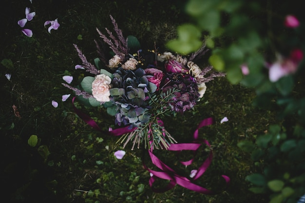 Rich wedding bouquet made of dark flowers and greenery lies on the green lawn