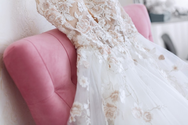 Rich white wedding dress hangs over the pink chair. morning of the bride in the hotel room. beautiful wedding dress on a hanger indoors in the bedroom. bride dress close up