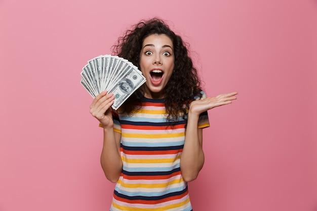 ピンクで隔離されたドルのお金のファンを保持している巻き毛の金持ちの女性20代