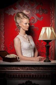 빅토리아 드레스와 인테리어에 부자 여자입니다. 풍부한 라이프 스타일. 빈티지와 역사