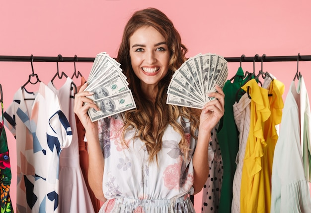 Богатая женщина, стоящая возле шкафа с денежными вентиляторами, изолированными на розовом