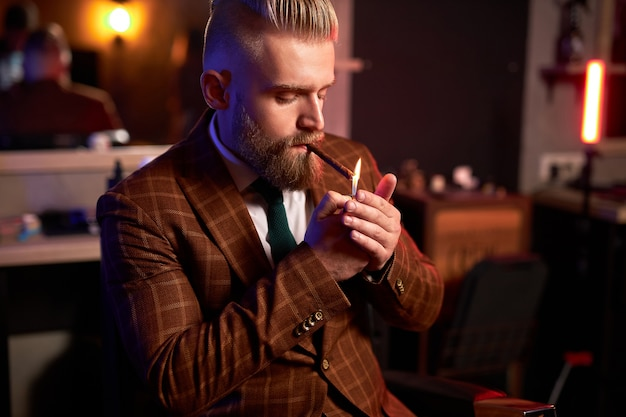 Rich young caucasian business man in suit smoke a cigar while sitting alone in dark room