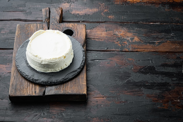 リコッタチーズ全体、木製のまな板、古い暗い木製のテーブル