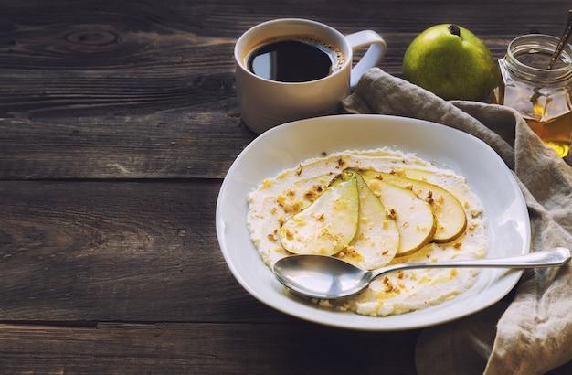 Сыр рикотта с грушей, измельченными грецкими орехами и медом на деревенском деревянном столе.