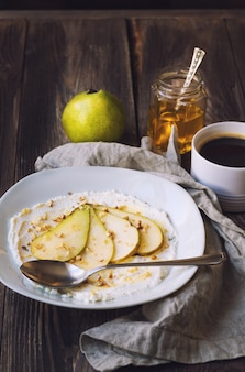 Ricotta cheese with pear,crushed walnuts and honey on rustic wooden table. healthy breakfast. Premium Photo