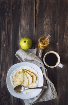 Ricotta cheese with pear, crushed walnuts and honey on rustic wooden