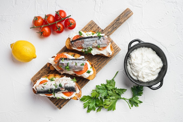 Ricotta sardine toast set, on white stone table background, top view flat lay