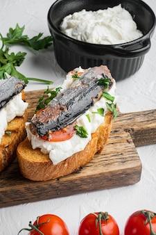 Ricotta sardine toast set, on white stone table background