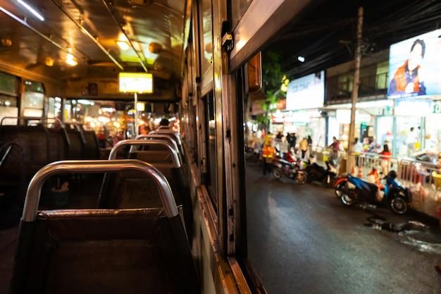 Ездить в пустом автобусе по ночному городу. интерьер городского автобуса. общественный транспорт в бангкоке