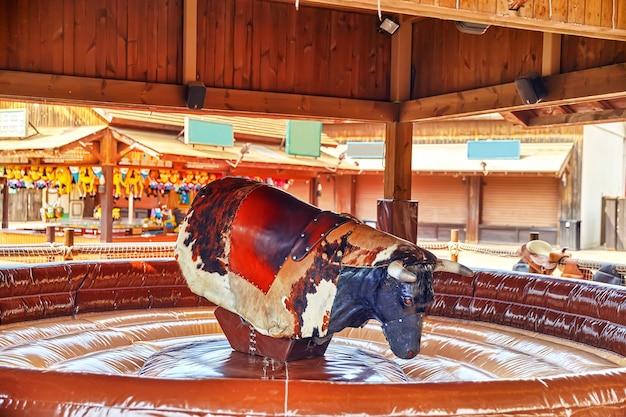 Катание на быке в парке аттракционов.