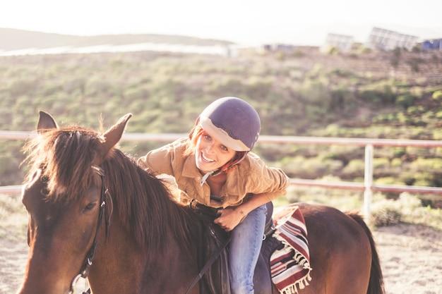 素敵な笑顔で美しく魅力的な若い女性のためにヘルメットをかぶってください。茶色の馬との余暇活動の屋外の女の子のためのジーンズとカジュアルな服。