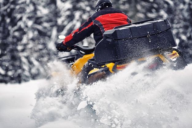 숲에서 겨울에 쿼드 바이크 경주에서 운전하는 라이더