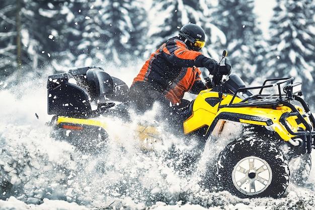 Всадник за рулем гонки на квадроциклах зимой в лесу