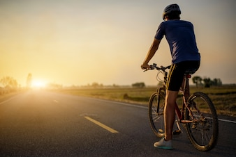 Rider is riding the bicycle on the road with sunset background