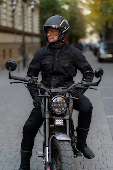 Rider man with beard and mustache in black fashion sunglasses and correct biker jacket sit on classic style racer motorbike at sunset. brutal fun urban lifestyle.