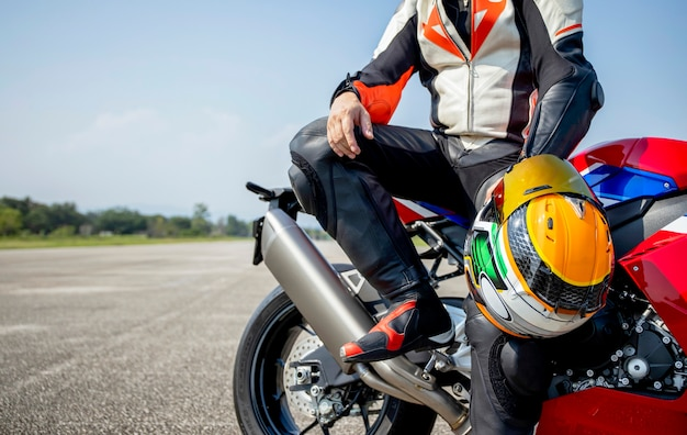 Мотоцикл всадника, держащий свой мотоциклетный шлем, сидя на большом велосипеде в дороге, езда