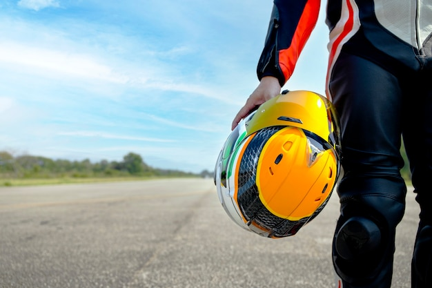 Мотоцикл всадника, держащий свой мотоциклетный шлем, идет по дороге, езда