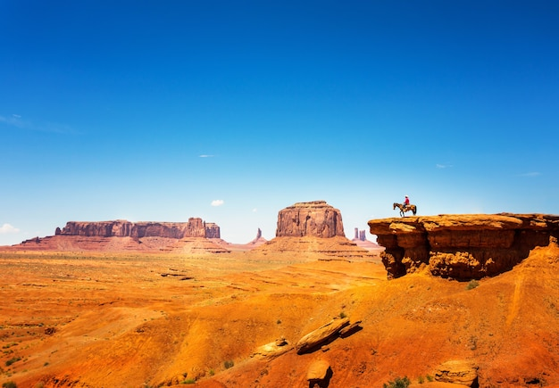 砂岩の山の頂上で馬に乗る