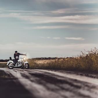 Всадник на мотоцикле за рулем на закате, байкер и мотоцикл готовы к поездке.