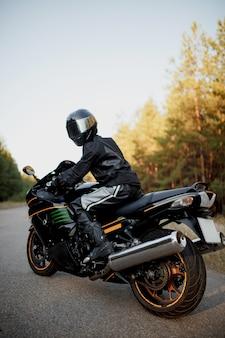 日没時に運転するバイクに乗る-あなたのテキスト、バイカー、バイクが乗る準備ができているスペース